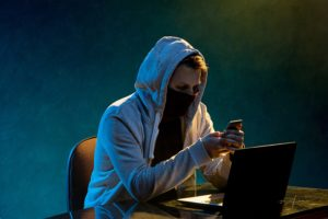 Hooded hacker using a laptop to perform a tax scam