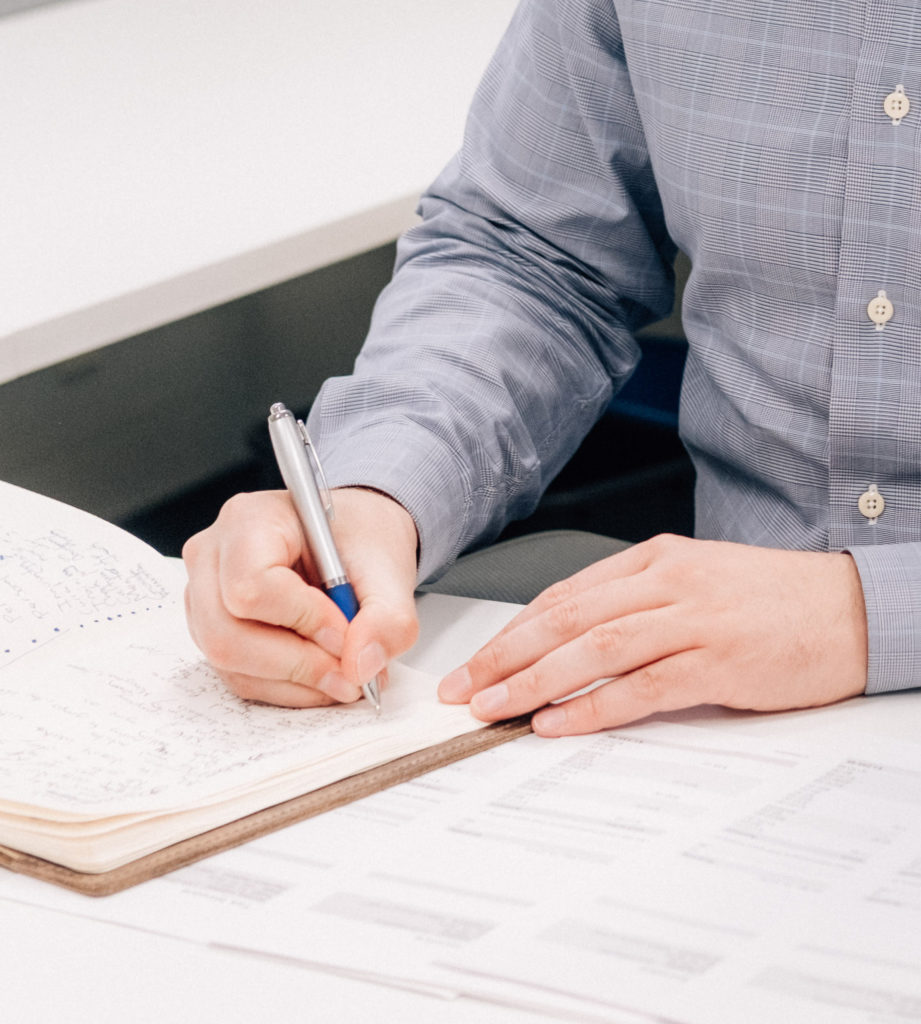 Man writing in notebook, bookkeeping by MBS Accountancy