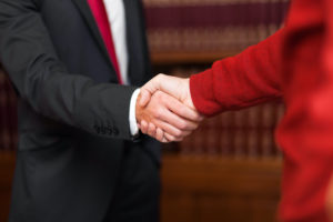 A businessman hiring a tax professional shakes their hand.