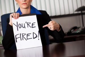 "Businesswoman holding a sign for their accountant that says ""you're fired."" Learn how to change accountants and get a better one in 2020."