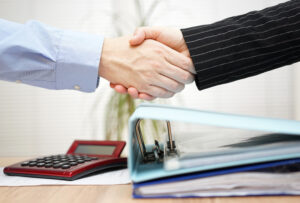 Two businesspeople shaking hands, illustrating the trust and partnership involved in outsourced accounting services.