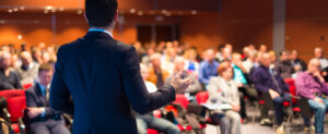 Speaker in front of a crowd at a business conference, illustrating internal training meetings.