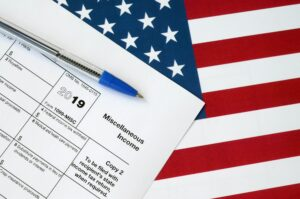Form 1099-misc Miscellaneous income and blue pen on United States flag