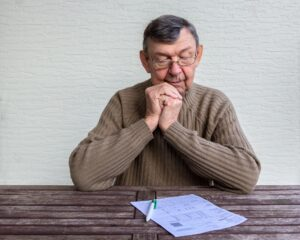 Portrait of elderly man sitting at table with white sheet of paper