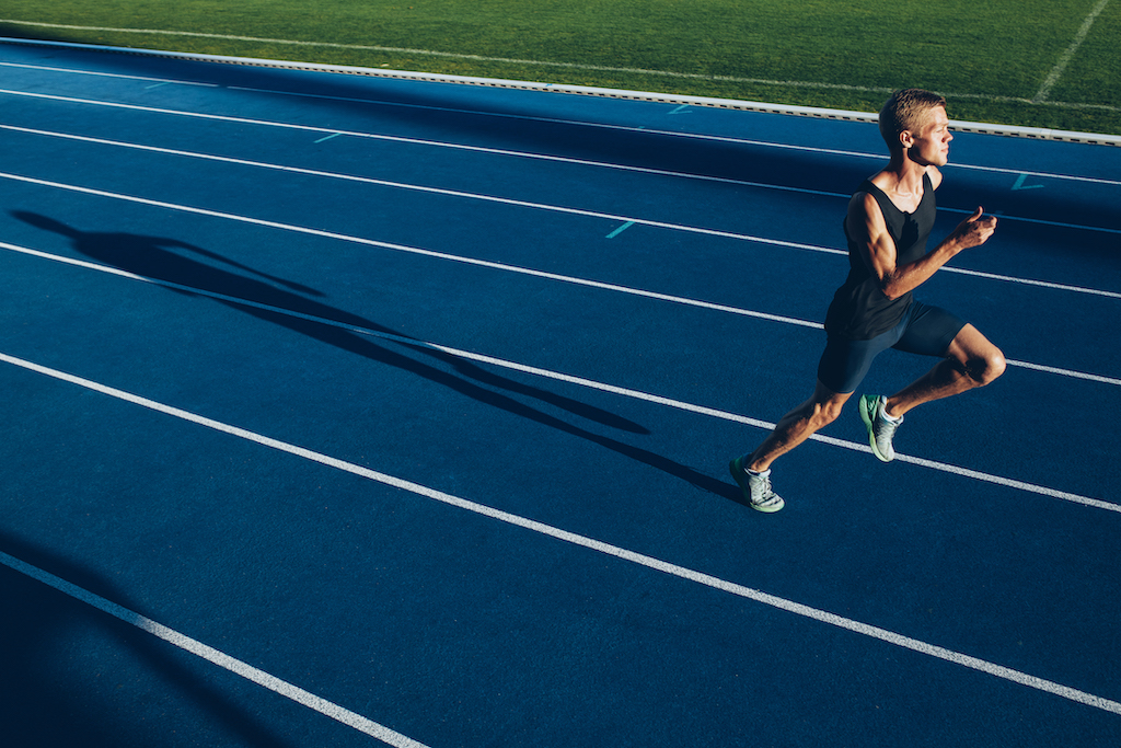 Runner sprinting along a racetrack, representing professional dedication.