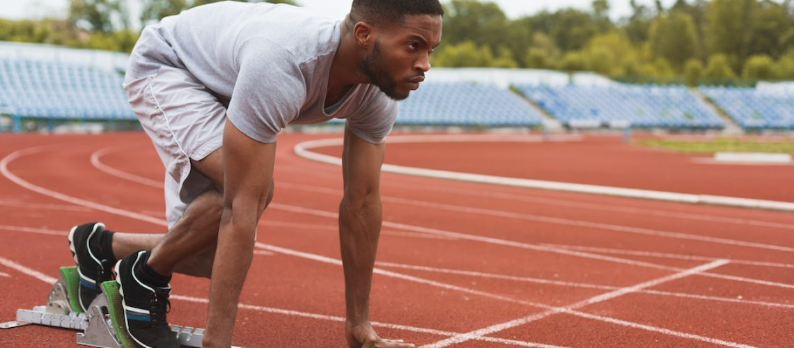 Fit afro-american sportsman on starting position, ready to run at the stadium