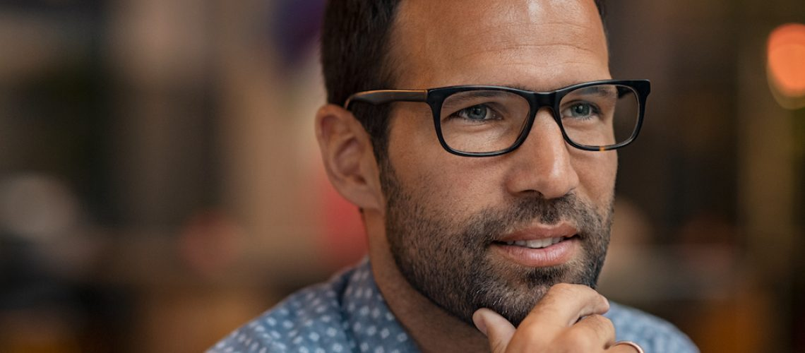 Thoughtful mid man wearing spectacles and looking away. Close up face of casual guy in eyeglasses with hand on chin thinking. Portrait of pensive young business man.