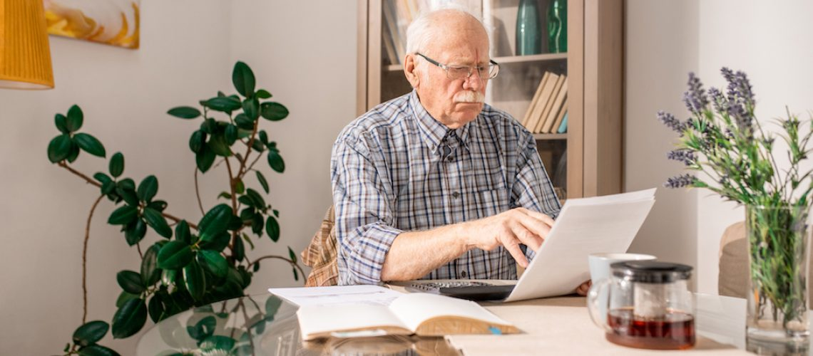 Portrait of senior man filling forms and paying taxes sitting at table at home, copy space
