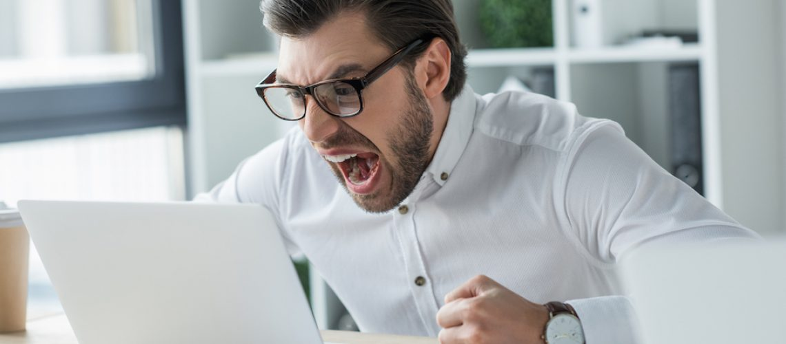 mad young businessman shouting at laptop in office