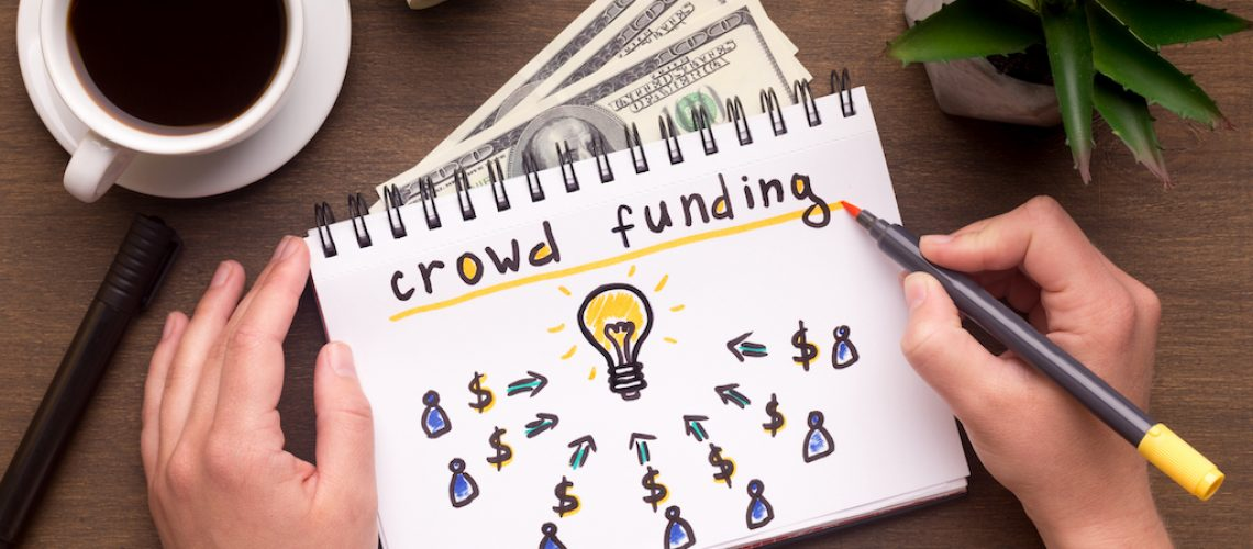 Business concept. Woman hand writing in notebook crowdfunding sign on table with dollars, panorama