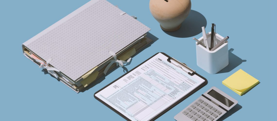 Filing the 1040 individual income tax return form on the office desk, finance and accounting concept, isometric objects