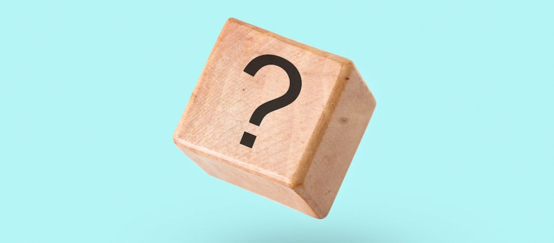 Wooden block on a turquoise background with a question mark - Cube with a question mark symbol in zero gravity and levitation - Concept of brainstorming and problem solving