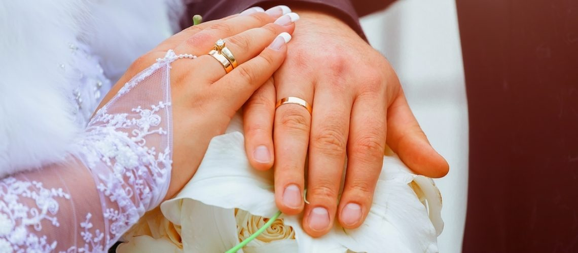 Close-up Bride and grooms hands with wedding rings golden ring on finger marriage day