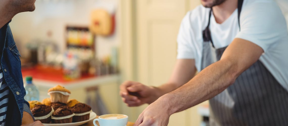 Male barista giving coffee to young customer at cafe