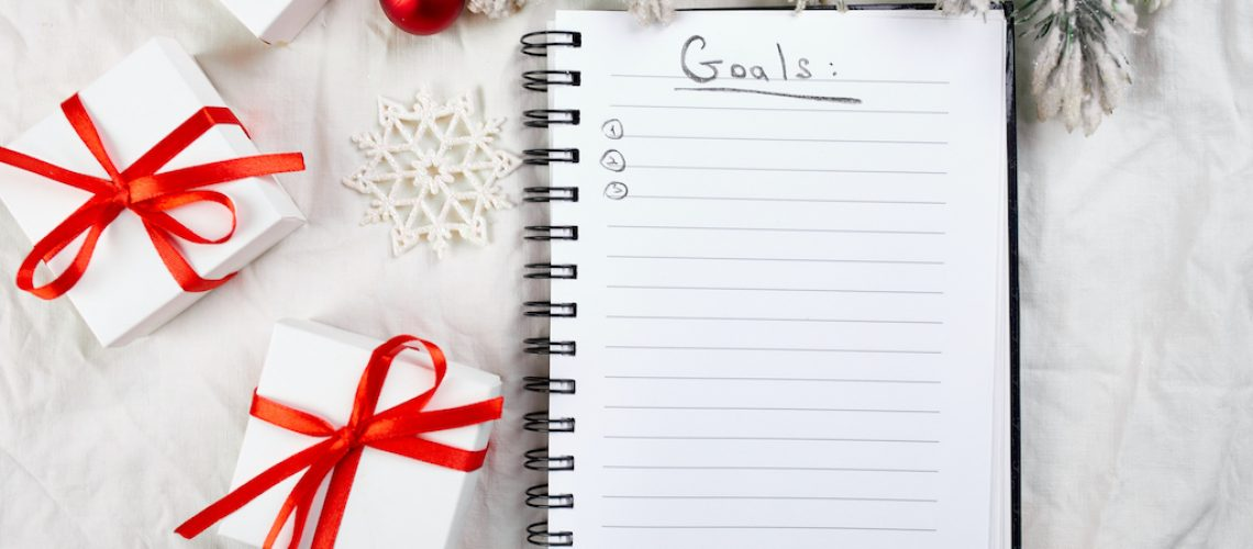 Top view of blank notebook for goals resolutions and christmas decoration on white textile linen tablecloth background, flat lay, copy space, new normal year.