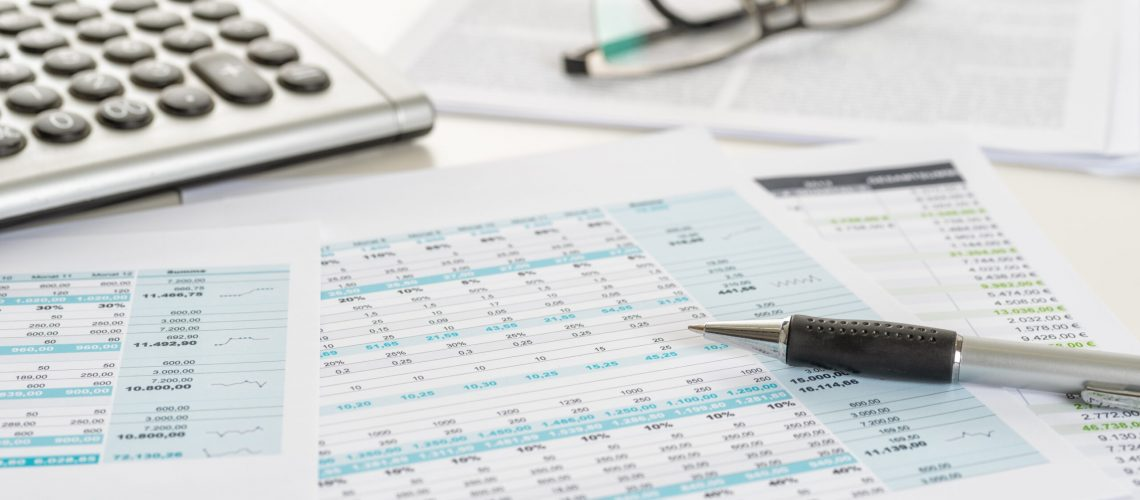 Paper spreadsheets and financial reports on a white desk with a pen and calculator that are used to make sure you don't overlook tax deductions and tax credits.