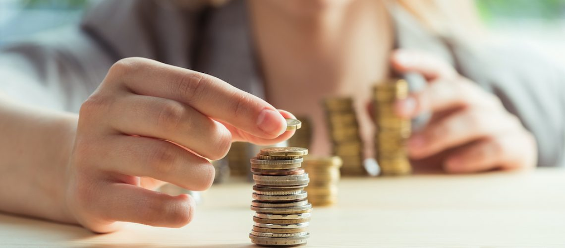 cropped view of woman stacking coins on table, investment concept