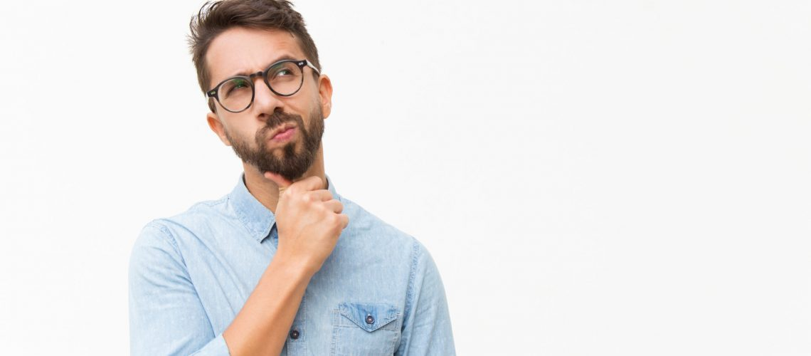 Thoughtful male customer thinking hard, looking away at copy space, leaning chin on hand. Handsome young man in casual shirt and glasses standing isolated over white background. Special offer concept