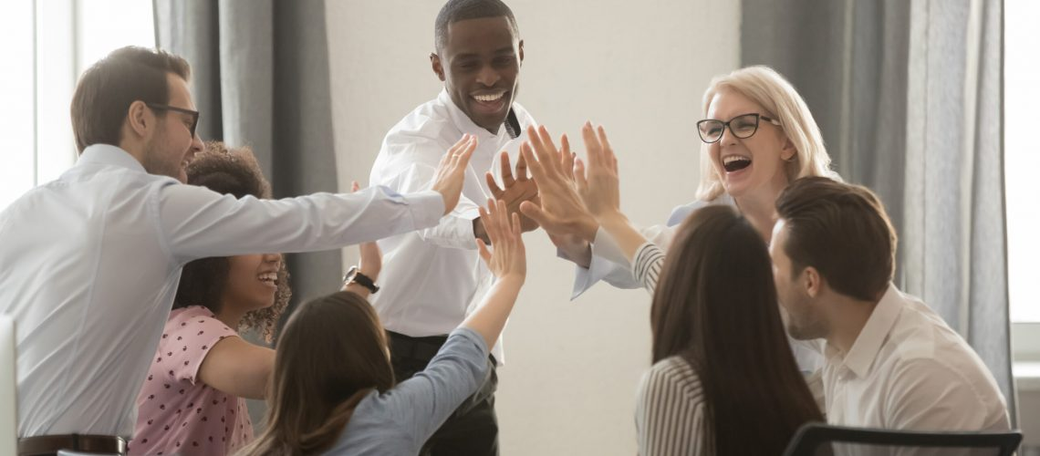 Excited multiracial colleagues give high five motivated for success