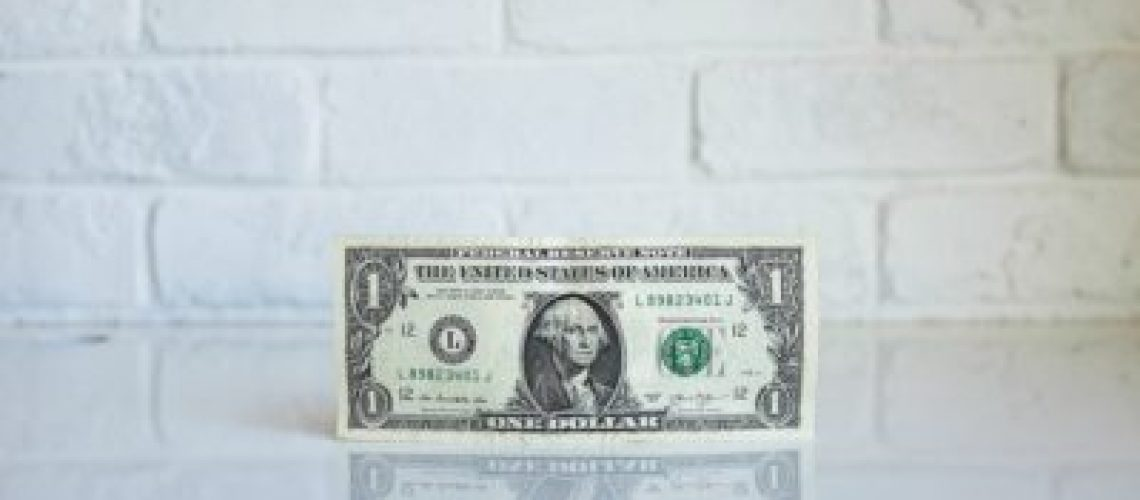 A dollar on a white reflective surface